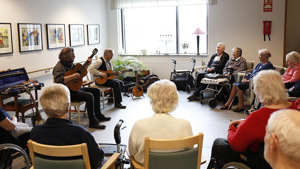 Två musiker som underhåller på ett demensboende